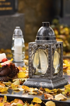 Beautiful autumn concept to the cemetery and Halloween. Candle in a lantern on the grave. Background for Halloween.