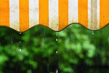 Rain. Awning on a balcony and drops of water on a natural colorful background during a spring day