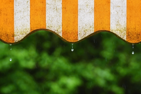 Rain. Awning on a balcony and drops of water on a natural colorful background during a spring day Stok Fotoğraf - 78591375
