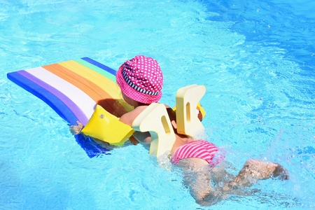 Little baby girl swims on the lilo in water at  hot sunny day. Summer holiday idyllic