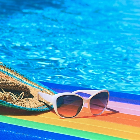 Sunglasses, lilo and hat on the water in hot sunny day. Summer background for traveling and vacation. Holiday idyllic.