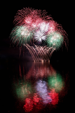 pyrotechnics: Firework. Beautiful colorful fireworks on the water surface with a clean black background. Fun festival and contest of Firefighters  Brno Dam - Czech Republic.