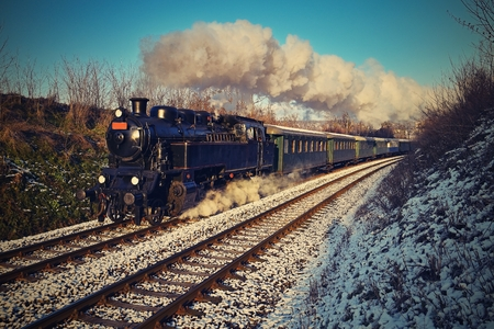 Beautiful old steam train with wagons running on rails at sunset. Excursions for children and parents on festive special days. Czech Republic Europe.