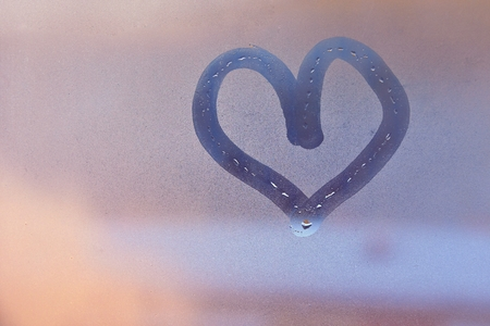 Heart painted with finger on foggy window