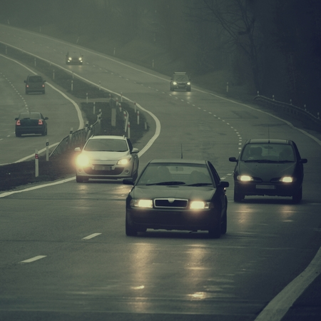 Bad weather driving - foggy hazy country road. Motorway - road traffic. Winter time. Фото со стока