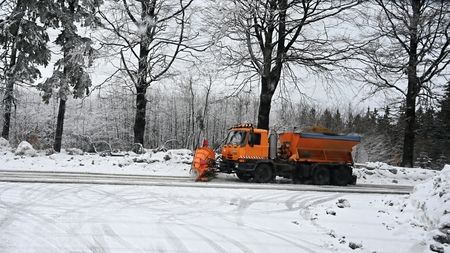 Front view of snowplow service truck - gritter car spreading salt on the road. Maintenance of roads in winter in the mountains.