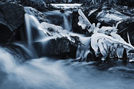 Blurred flowing water in winter creek. Beautiful photo of winter nature in the forest. Reklamní fotografie