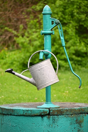 Classic hand pump for water - well with kettle for watering the garden.