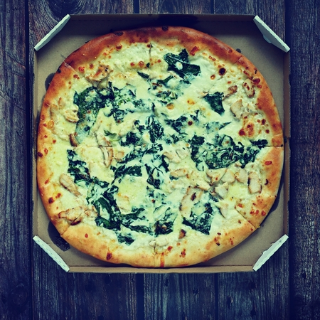 Delicious fresh pizza served on wooden table. Pizza with cream and spinach ready for delivery in a box.