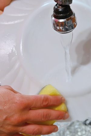 Hand washing dishes. Hand with sponge and sink in kitchen washing dirty dishes - plate.
