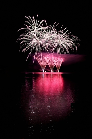 Beautiful colorful fireworks on the water surface. Night scene. Concept for holidays and celebrations.