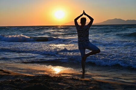 Woman meditates - relaxes at sunset by the sea on the beach. Concept for yoga, health and spa.