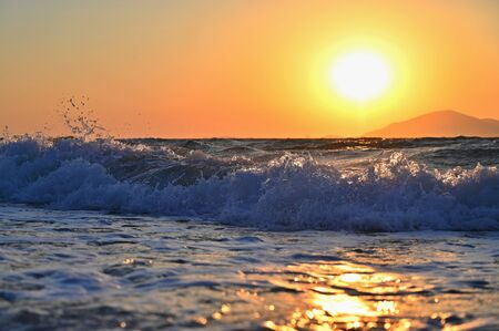 Beautiful sunset with sea and waves. Natural colorful background. Concept for summer and sea vacation. Greece - island of Kos.