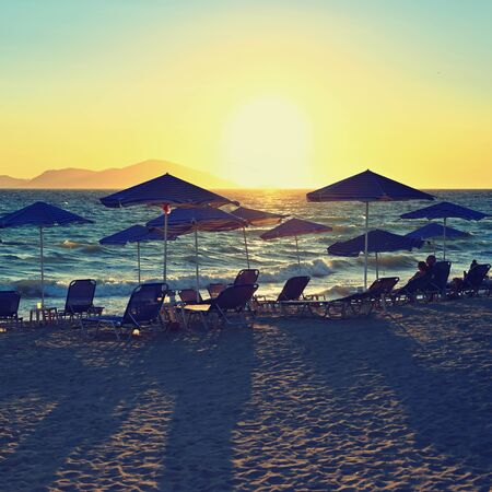 Sunbeds and umbrella on the beach at sunset by the sea. Beautiful concept for vacation, summer holidays and travel.