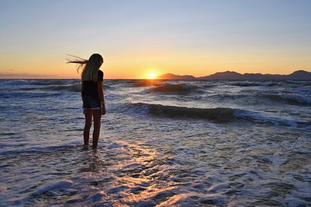 Young girl on the beach near the sea at sunset.