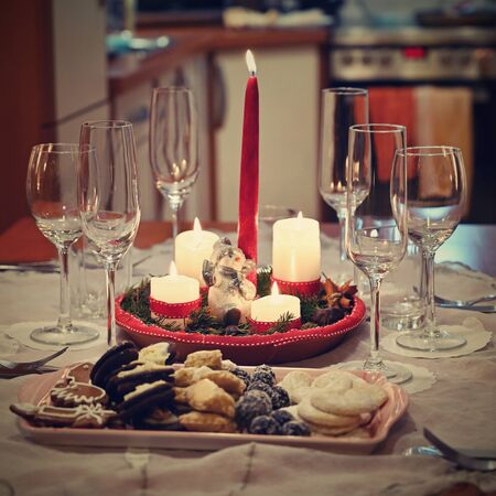 Beautifully set table for Christmas holidays. Candies, candles and Christmas decorations - decorated home on Christmas Eve. Zdjęcie Seryjne