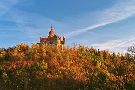Beautiful old romantic Bouzov castle at sunset with autumn landscape. 新聞圖片