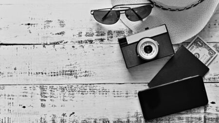 Items for summer vacation: a camera, passport,smartphone, money, hat, sunglasses. Wooden background, top view with Copy space. Beautiful summer concept for travel and vacation-holidays. Standard-Bild - 147043895