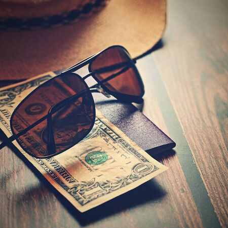 Items for summer vacation: a camera, passport,smartphone, money, hat, sunglasses. Wooden background, top view with Copy space. Beautiful summer concept for travel. Standard-Bild - 147044837