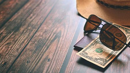 Items for summer vacation: a camera, passport,smartphone, money, hat, sunglasses. Wooden background, top view with Copy space. Beautiful summer concept for travel.