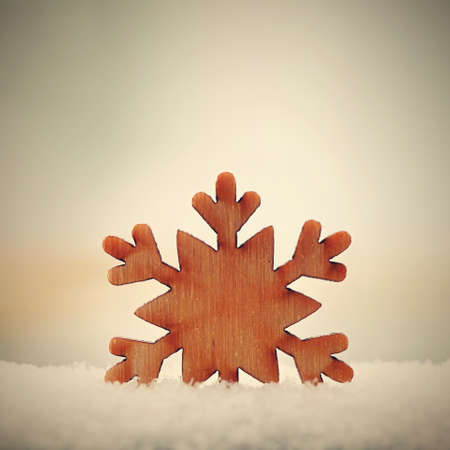 Christmas background. Christmas tree decoration - beautiful natural wooden snowflake with real snow. Background for winter and holiday.