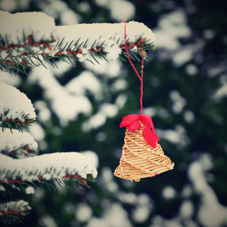 Beautiful natural Christmas decorations made of straw on a snowy Christmas tree. Winter nature colorful outdoor background for the holidays.