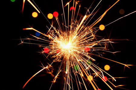 Sparkler with beautiful abstract colorful background. Concept for Christmas and Happy New Year 2021.