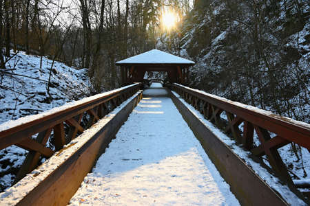 Beautiful snowy wooden bridge with a path for hiking. Winter season with snow and sun. Reklamní fotografie