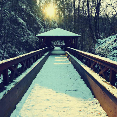 Beautiful snowy wooden bridge with a path for hiking. Winter season with snow and sun. Zdjęcie Seryjne - 163506312