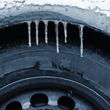 Frozen car with a tire. Icicles on the car. Concept for winter and dangerous traffic of cars on the road. Standard-Bild - 163806147