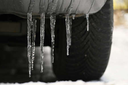 Beautiful icicles on the car. Concept for winter and dangerous winter traffic of cars on the road.