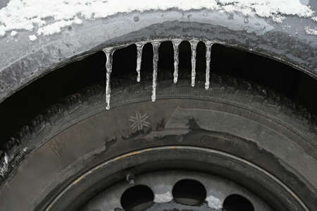 Frozen car with a tire. Icicles on the car. Concept for winter and dangerous traffic of cars on the road.