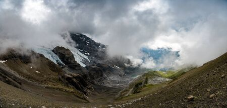 landscape at Hohtürli with Oeschinensee in the distance in misty clouds while hiking
