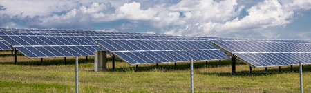 Solar panels on green grass with blue sky photo