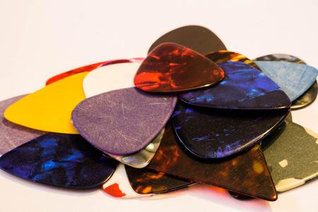 Multi-colored guitar pick on white background photo