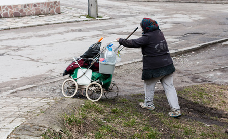 old homeless woman pushing a broken stroller