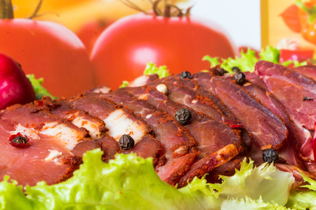 Cut pieces of smoked meat with lettuce, radish and pepper photo