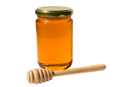 jar with honey and wooden spoon with clipping path photo