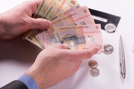 Ðœan holding Romanian banknotes on a white background