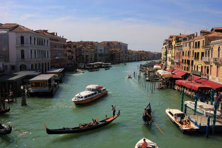 Gondolas and boats take tourists along the old historic buildings of the Grand Canal, Venice, Italy Standard-Bild - 131712489