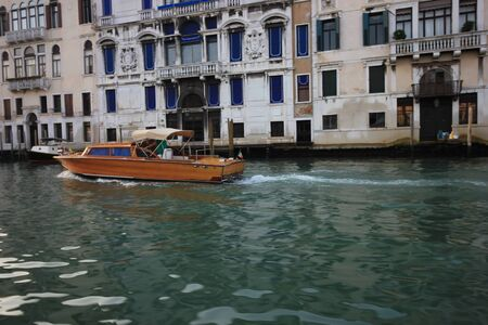Gondolas and boats take tourists along the old historic buildings of the Grand Canal, Venice, Italy Standard-Bild - 131712522