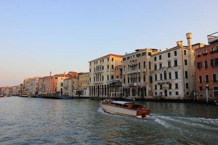 Gondolas and boats take tourists along the old historic buildings of the Grand Canal, Venice, Italy Standard-Bild - 131712575