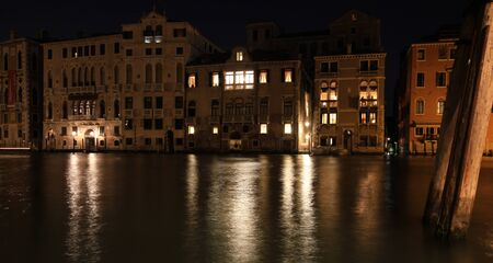 Venice at night. The lights of the city are reflected in the quiet Venetian canals. Stock Photo