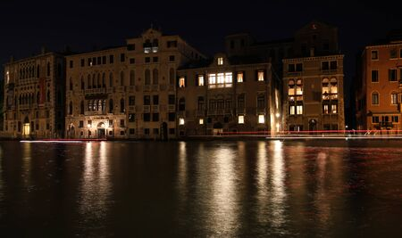 Venice at night. The lights of the city are reflected in the quiet Venetian canals. Standard-Bild - 131712727