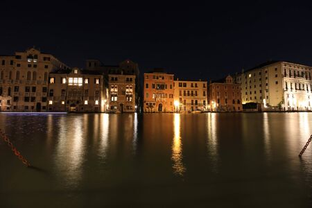 Venice at night. The lights of the city are reflected in the quiet Venetian canals. 免版税图像