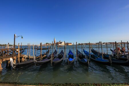 Pier gondolas await tourists for a romantic stroll through the canals of Venice Standard-Bild - 131712736