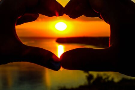 Hands show the shape of the heart against the backdrop of the sunset over the sea Stock Photo
