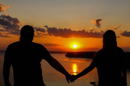 Silhouette of lovers in the sunset over the sea. A guy and a girl against the background of a bright sunset holding hands.