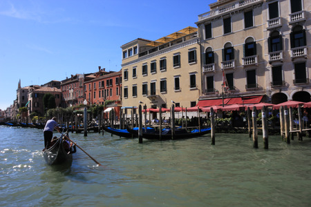 Gondolas and boats take tourists along the old historic buildings of the Grand Canal, Venice, Italy