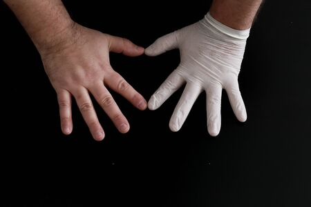 Two hands show heart shape on a black background. One hand in a medical glove.